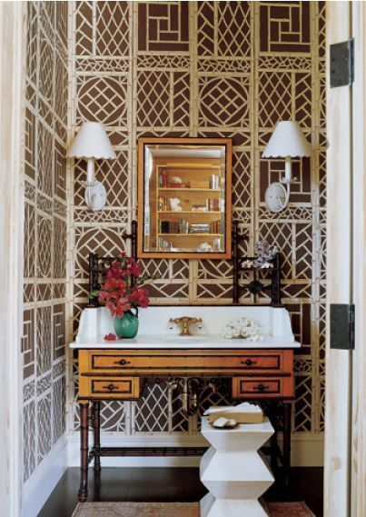 The brown and white wallpaper layered with the vintage vanity makes this powder room a knock out (Mark D Sikes).