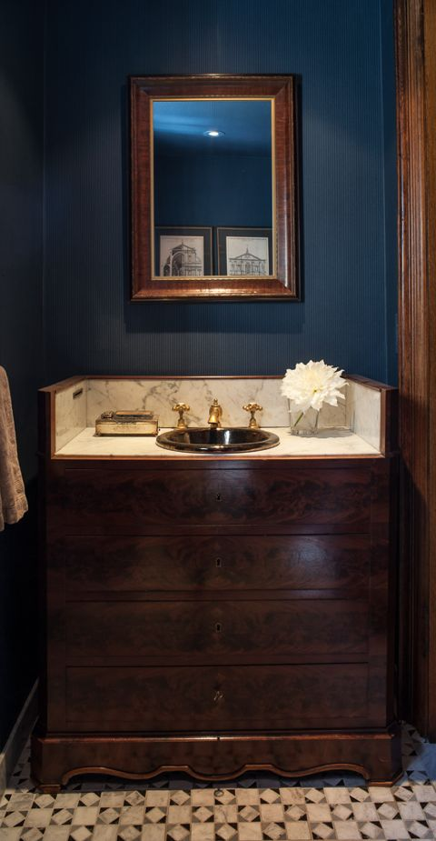 The indigo pinstriped wallpaper is a foil for this antique cabinet-turned-vanity for this powder room. It pairs beautifully with the custom designed mosaic floor - so rich and lively.  (Casey Design/Planning Group Inc. - Photos by Ted Yarwood).