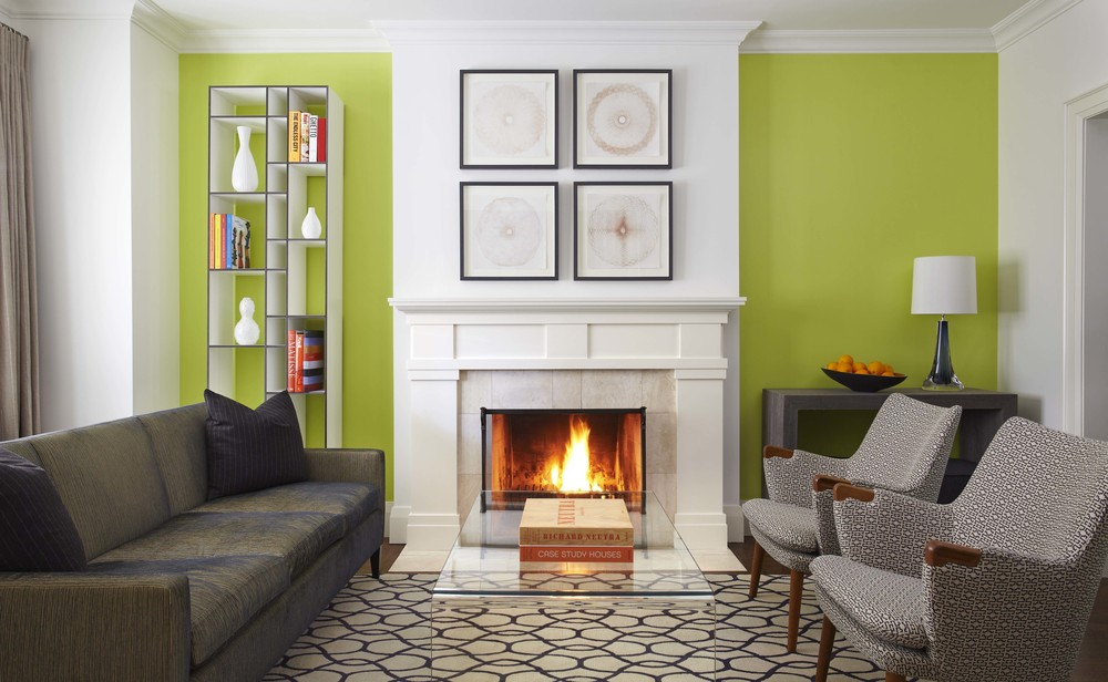 The green walls and fireplace act as the focal point to this room. Aligning furniture in a way that directs the eye to the focal point creates a sense of hierarchy and balance in this room. (Casey Design / Planning Group Inc. - photograph by Michael Graydon)