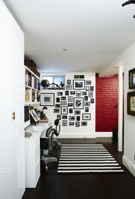 A painted red brick wall adds some colour to the black and white home office. A wall of picture frames and a striped area rug creates a sense of character in the space. (Casey Design / Planning Group Inc. - photograph by Angus Fergusson)