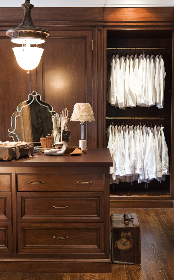 Rich, medium toned wood surrounds this master closet, to create a sense of unity. A large island centres and acts as a functional working area for our clients. (Casey Design / Planning Group Inc. - photograph by Ted Yarwood)