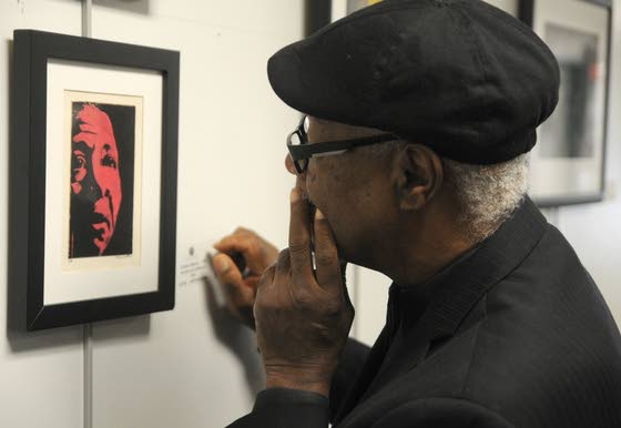 "African American Heritage Museum founder and president Ralph Hunter examines Schwachter's painting of ""Lonnie Johnson"""