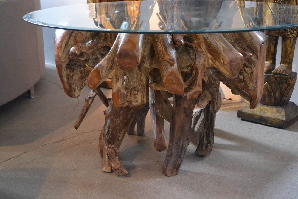 authentically sculpted teak root dining table with glass top.