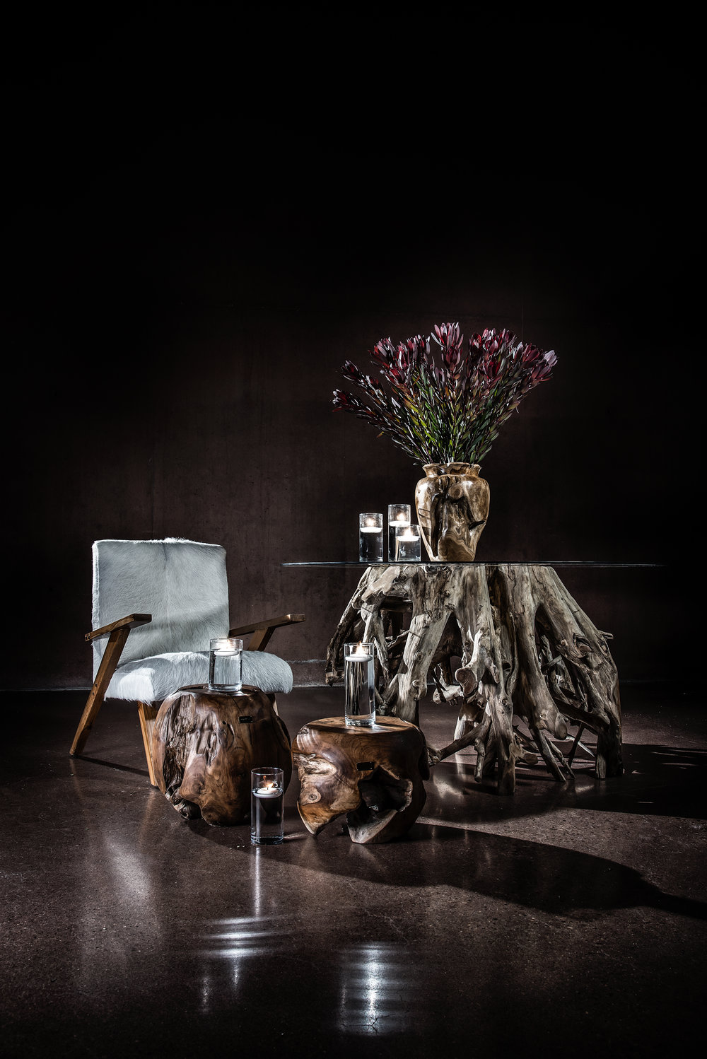 A beautiful combination of textures: Teak Root Tables, Maude Hair on Hide Chairs and the high shiny of glass.