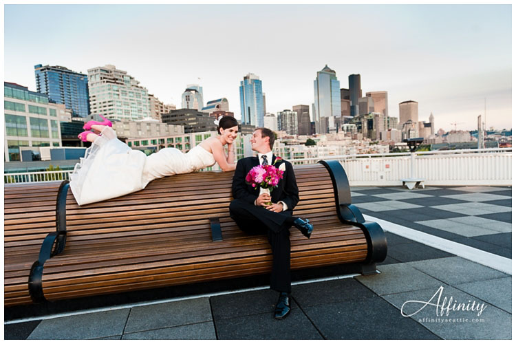035-bride-lays-bench-groom-with-flowers-seattle-skyline.jpg