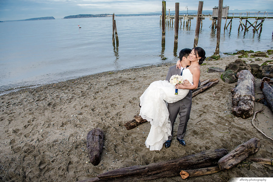 15-groom-picking-up-bride-beach-piers-sand.jpg