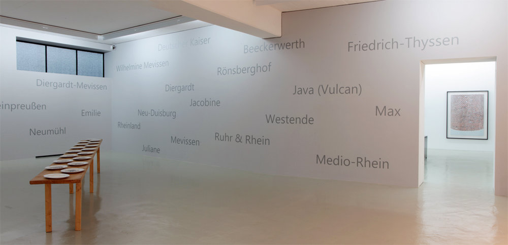 "Glück Auf I  ,  table with porcelain plates with portraits of coal miners (collection Museum DKM); wall (2018): names of all locations and names of coal mines in Duisburg  The table was exhibited first in 1991 at Zeche Rheinpreussen, Moers just before the closing of the mine; the miners shown on the plates were photographed after their last shift- now exhibited again in 2018 for the exhibition project  ""Kunst und Kohle - Die schwarze Seite""  at Museum DKM, Duisburg/Germany"