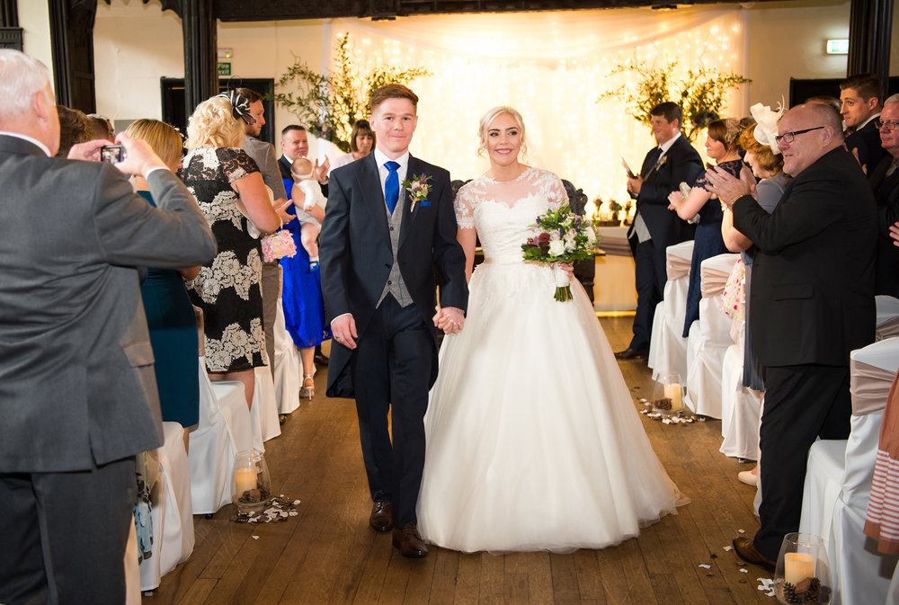 The married couple walk out of the Great Hall at Samlesbury Hall