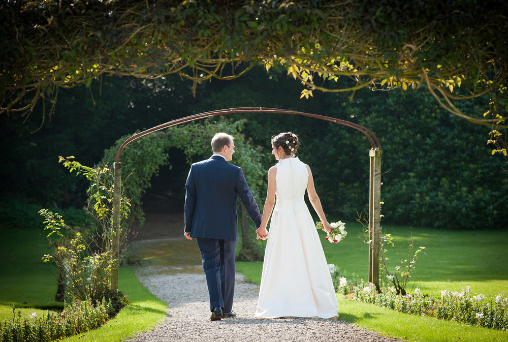 Bride & Groom walking through the gardens at Leighton Hall