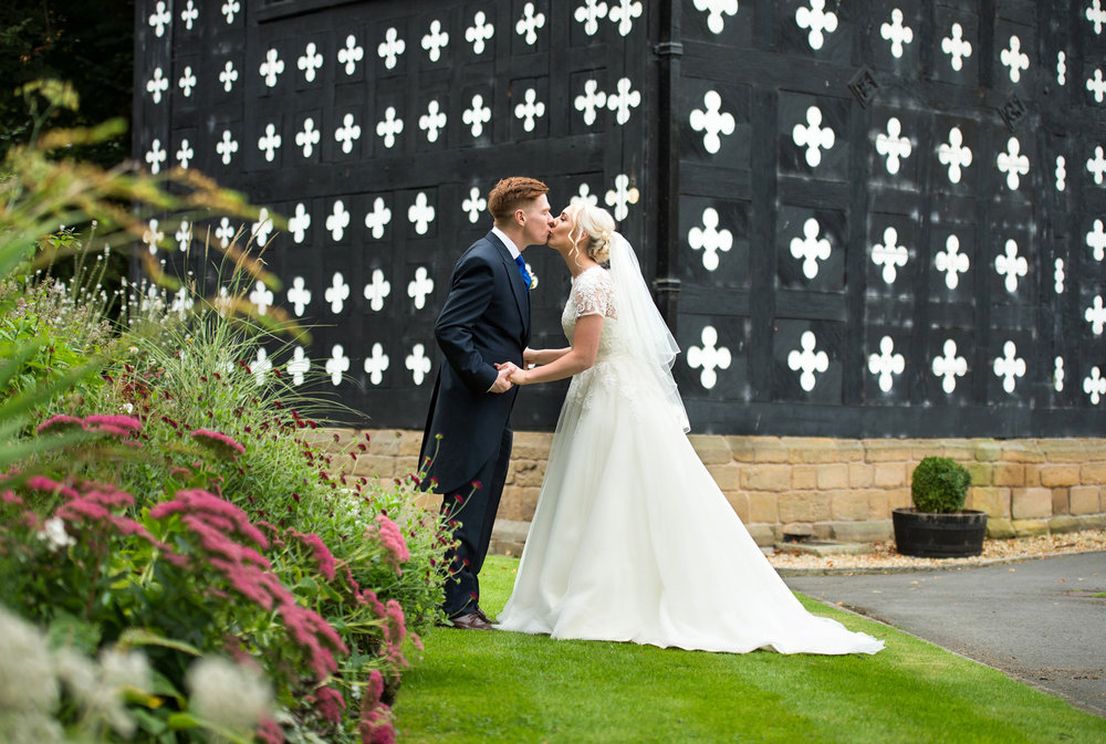 Wedding photograph of a bride and groom outside Samlesbury Hall