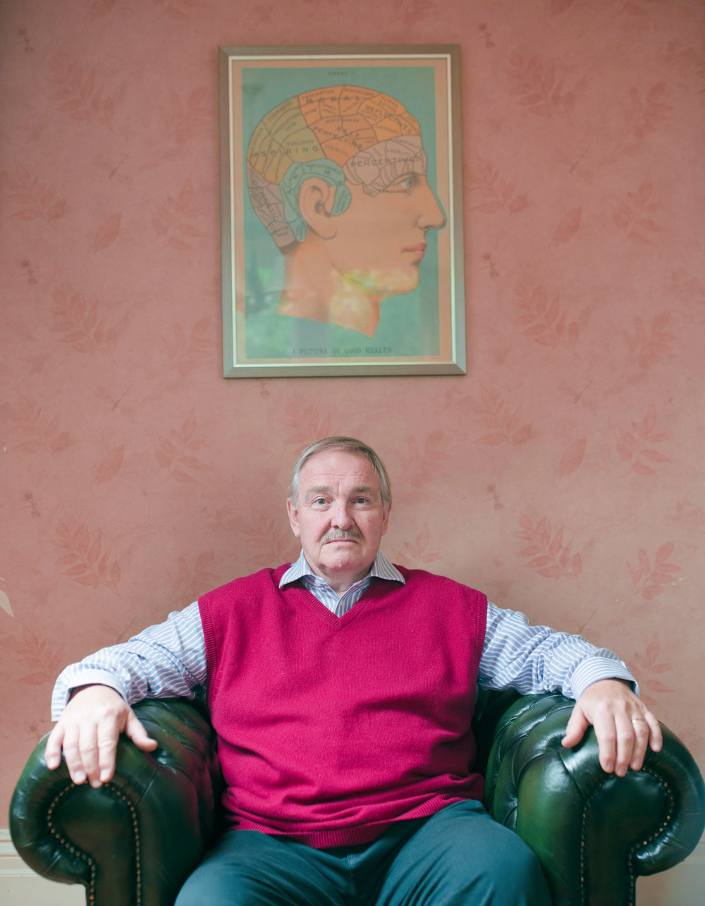 David Nutt photographed sitting under a Phrenology poster