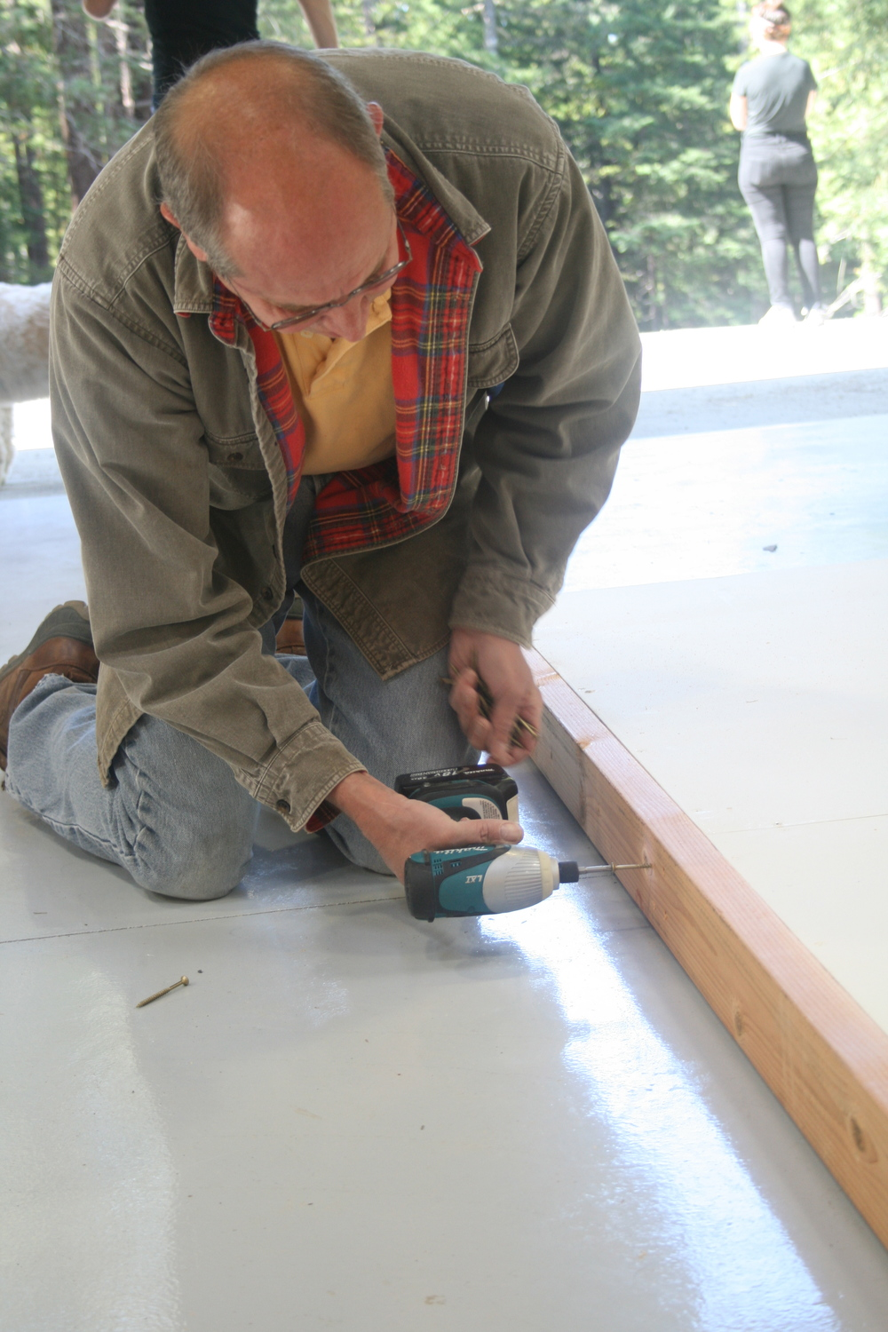 Board member Ray Feeney finishes securing the 2x4 frame around our walls