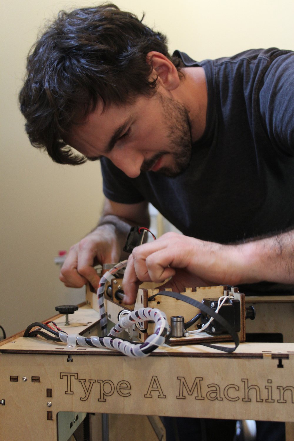 Bryan Allen adjusts a piece on one of the 6 Type A Machines printers working to produce the Smith|Allen sculpture