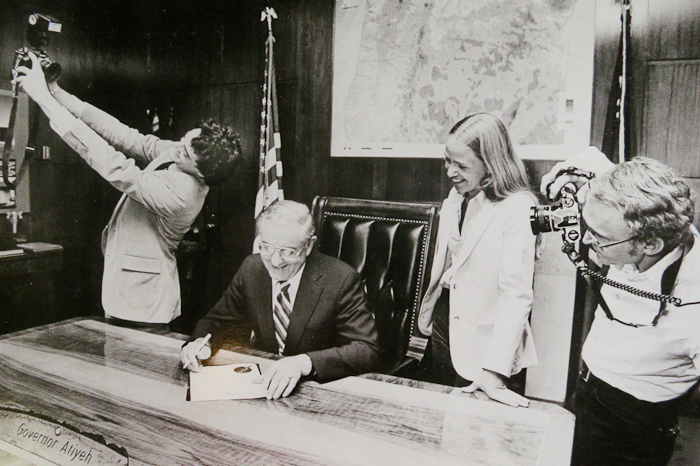 "Photographers Mike Lloyd, Cathy Cheney and Michal Thompson celebrate as Governor Atiyeh proclaims July 15, 1983 ""Oregon Photojournalism Day."""