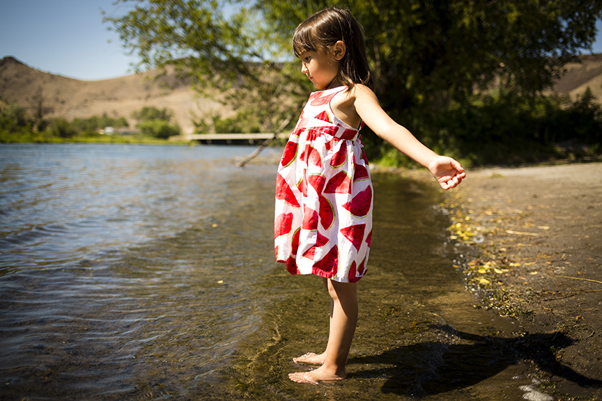 4-year-old Yuna dips her toes in the Deschutes River in Warm Springs.