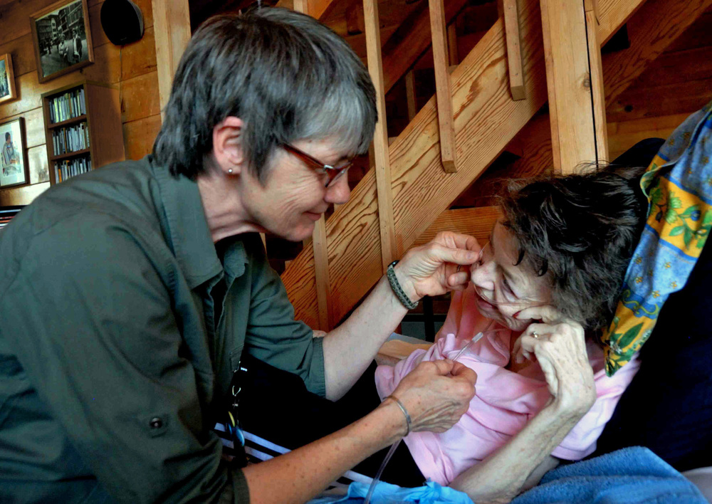 Cindy Andexle, nurse's aide with Willamette Valley Hospice in Salem, assists Elena Lewin. Elena was given two weeks to live in November of 2011. More than 600 days later, she is still with us. Photo by Gerry Lewin