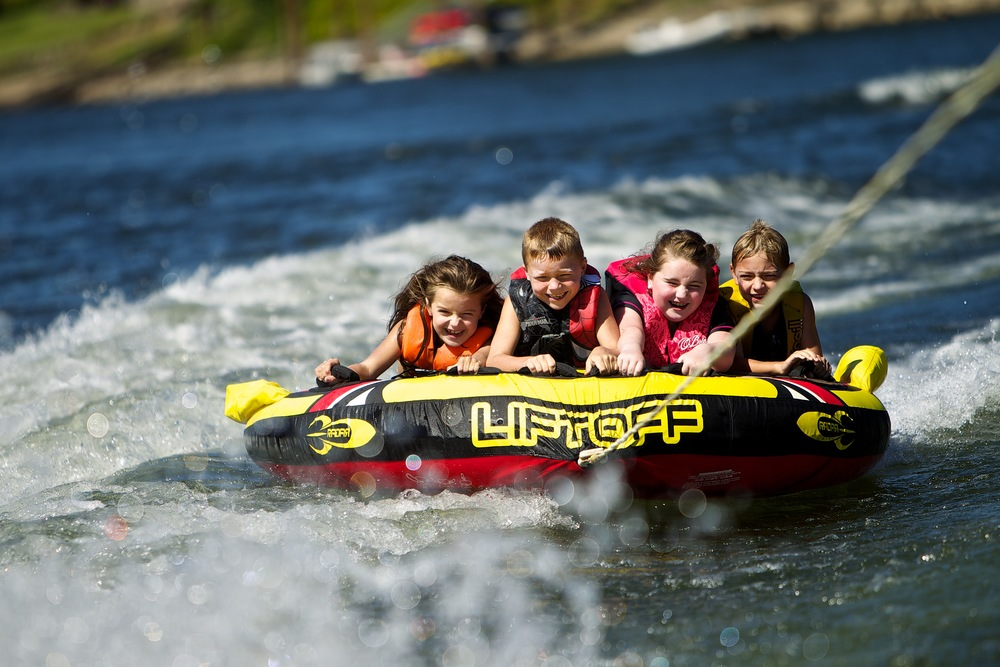 Emma McDonald (8), Ben Rose (7), Jordyn Mitchelldyer (8) and Chase McDonald (7) ride on a tube on the Willamette River in Clackamas County. Photo by Craig Mitchelldyer
