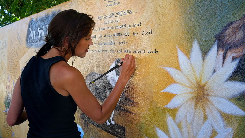 Although not one of the original artists, Lissa Jensen retouches blemishes on Silverton Bobbie's Memorial Mural on Water Street in downtown.  Photo by Stewart Harvey