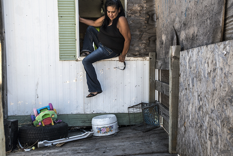 A resident climbs out of her window, demonstrating how she enters and leaves her home. The door is barricaded to keep out intruders.  Photo by Joe Cantrell