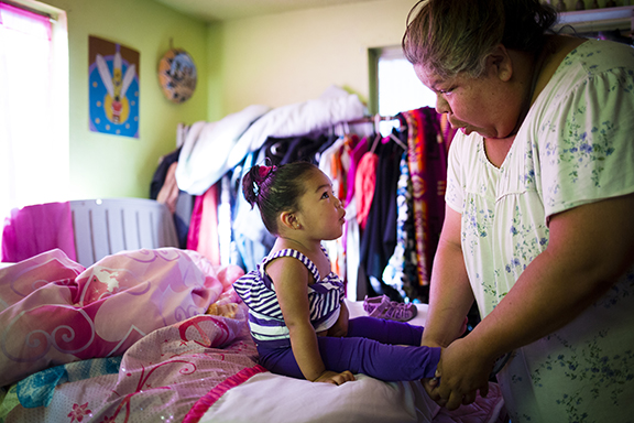 Charlie Green dresses her foster daughter Cadrienne WaiWaipam for day care. They both live with Charlie's mother Lucinda, along with nine other family members.  Photo by Leah Nash