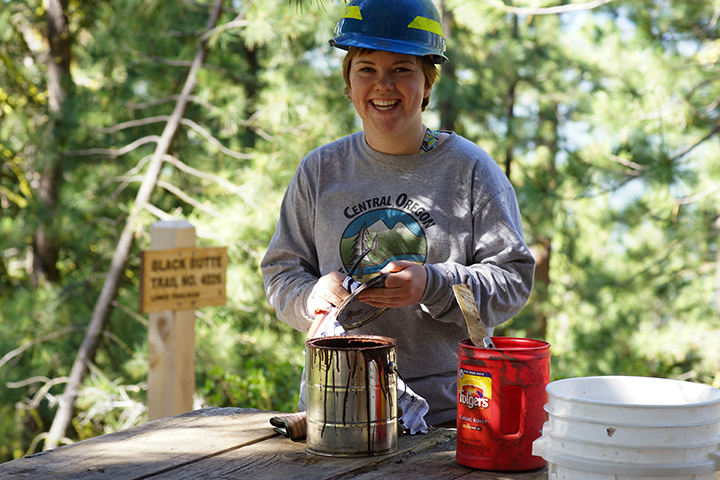 Scout Miller mixes paint for a fresh coat being applied on the information kiosk. She is part of a team of Youth Conservation Corps young adults led by 2nd generation USFS employee Rikki Glick that was working to restore trailhead facilities at the beginning of the Black Butte FIre Lookout trail. The YCC has introduced young Americans to conservation opportunities in public lands since the program was created in 1970.  Photo by Gary Miller