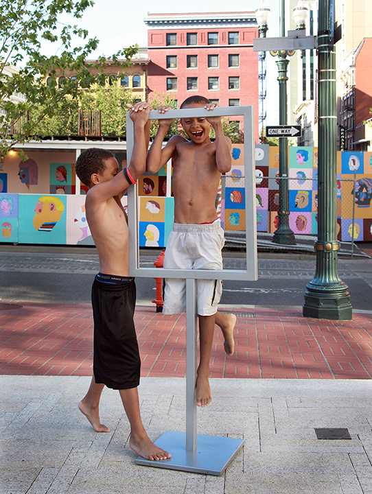 Young boys play on an empty sign holder at Director Park in downtown Portland. Photo by Cathy Cheney