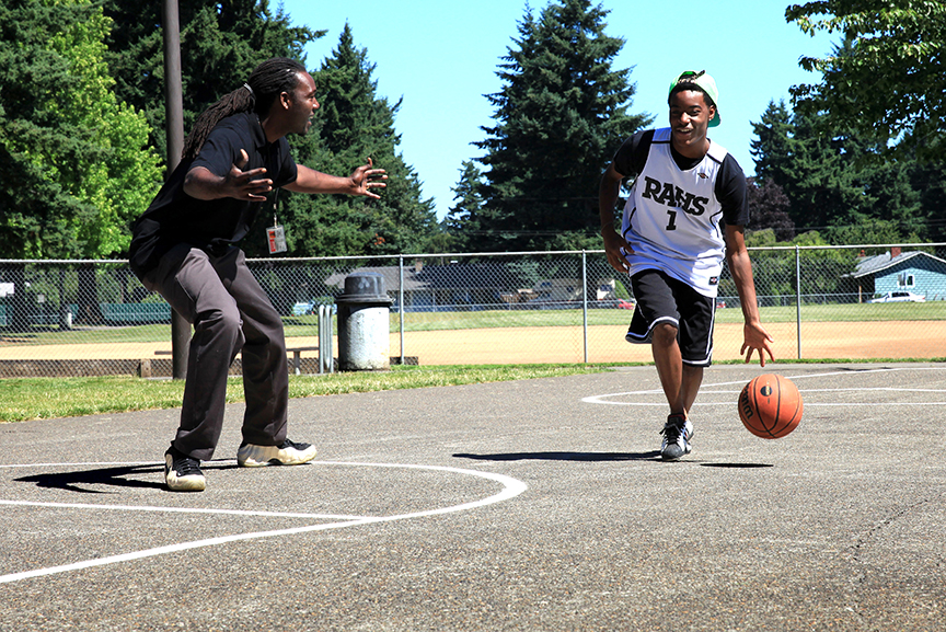 Portland Opportunities Industrial Center (POIC), East Portland Rosemary Anderson High School, is a non-profit educational and workforce training organization that works with disenfranchised youth in Northeast and East Multnomah county. Teacher Jay Williams plays basketball with student Deon Sims. Photo by Jan Landis