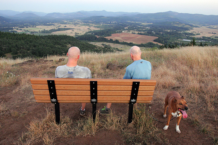 Andrew Dow (left) and his father, Doug, (and Jack the dog) enjoy the view from Mount Pisgah shortly after sunset. The hill, rising about a thousand feet above the surrounding area, is a popular hiking spot, offering panoramic views of the southern Willamette Valley. Photo by Rob Romig