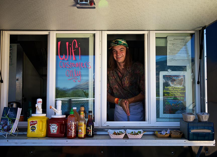 Zack Olmstead delivers some fish tacos to a customer from a food booth on the docks at Hood River.  Photo by Tom Boyd