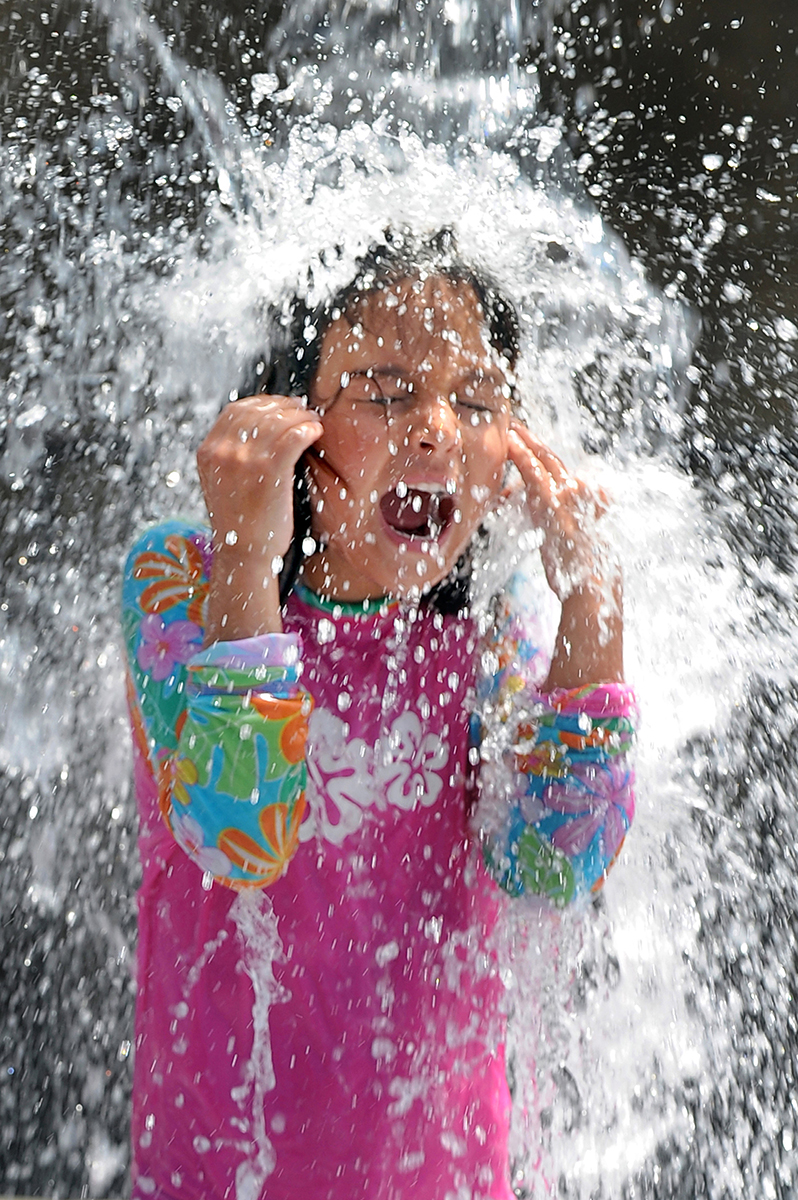 Mackensie Locklin (6) of Ashland stays cool as temperatures near 100 degrees in Ashland's Garfield Park.  Photo by Bob Pennell