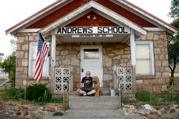 Self-portrait with his dog Phoebe in front of the old Andrews School in Andrews. Photo by John Simpkins