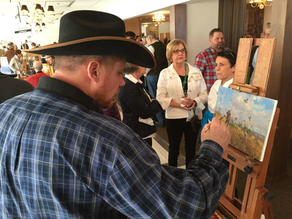Artist  Chad Poppleton  finishes a painting to be auctioned while interested buyers eagerly watch.