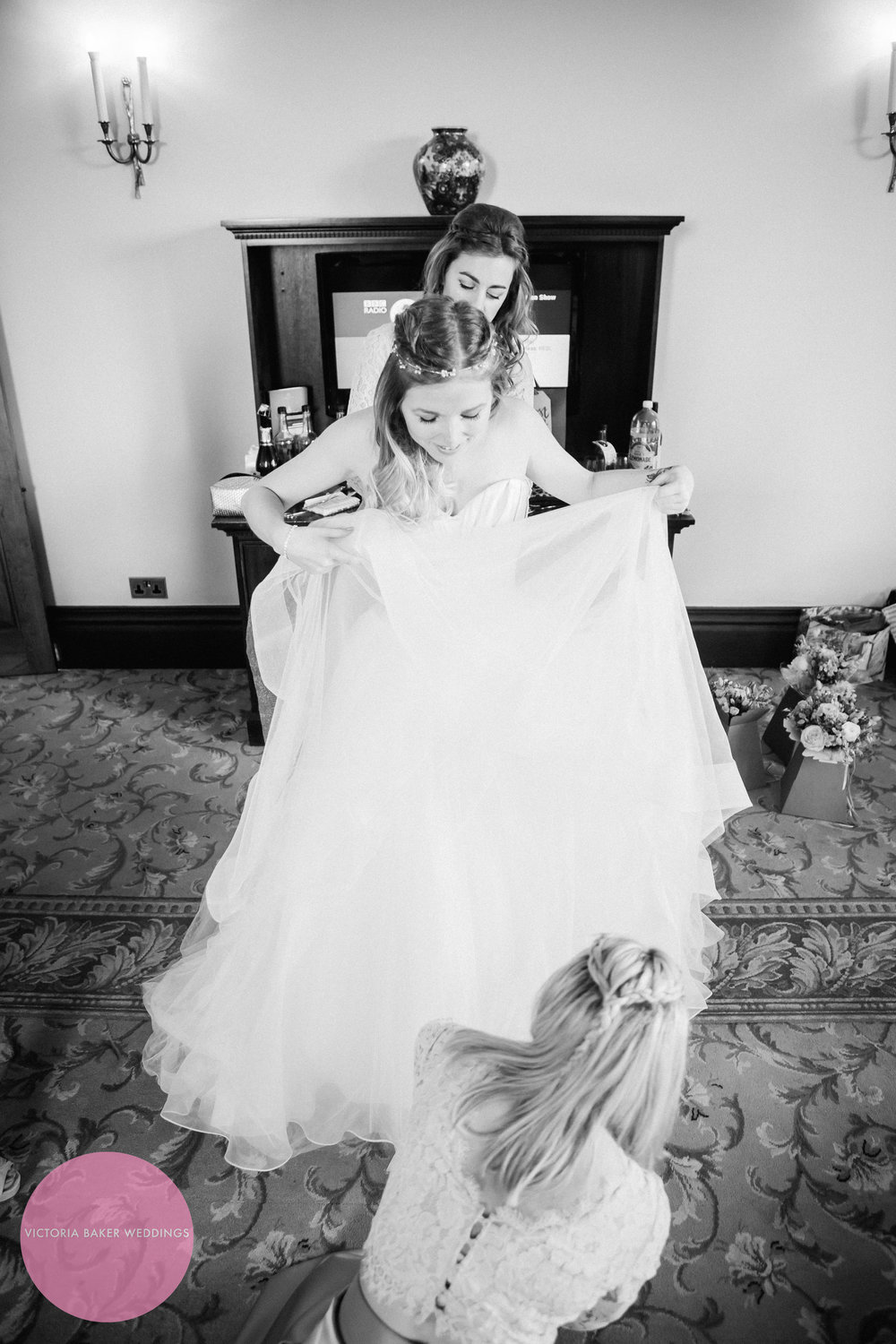 Bride getting into wedding dress at Oulton Hall