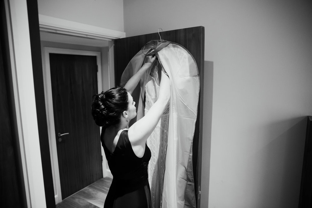 Bridesmaid getting wedding dress out for bride