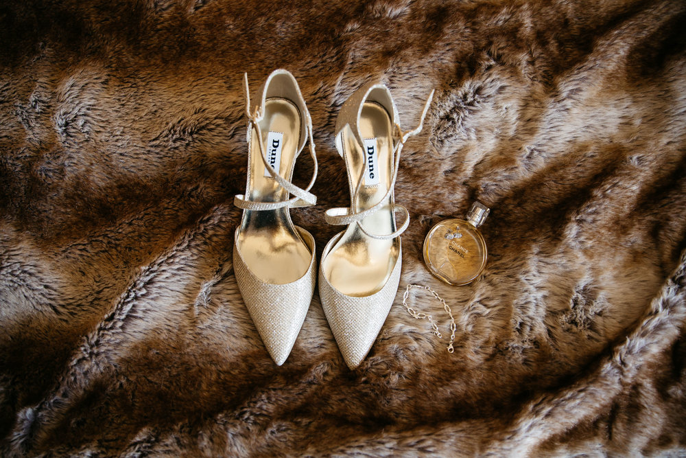 Wedding shoe and accessories on bed