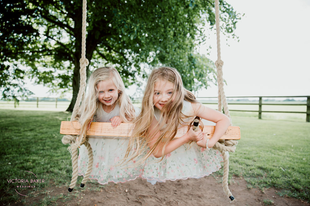 Flower Girls on swing at Barmbyfield Barn | Creative Yorkshire Wedding Photographer