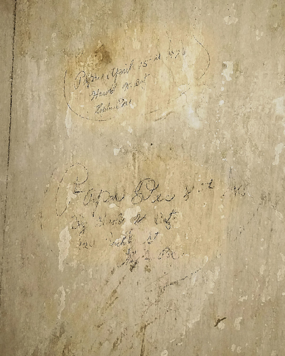 Found this writing under the wallpaper in the hallway. It's difficult to make out but it looks like the dates of when they papered the wall.