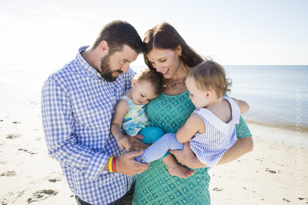 Candid moment of family of four at beach in the sun with sparking water behind them