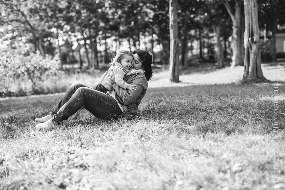 Candid mom and daughter moment laughing and playing on the grass