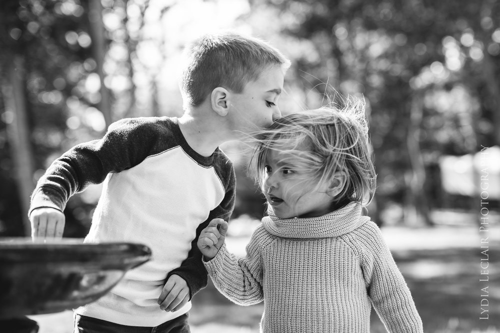 Sweet black and white sibling kiss in the woods