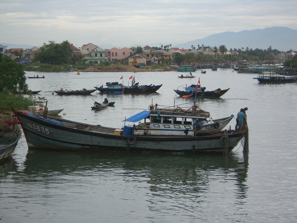 boats with Hoi An's old city in the background