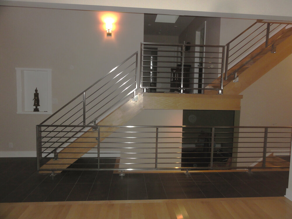 Stainless steel horizontal railing and wooden staircase