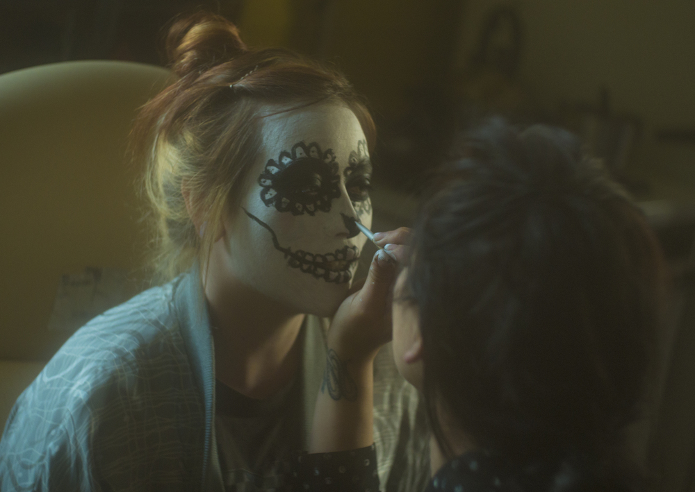 Director Emily Esperanza applying sugar skull makeup to Maureen Neer of Soddy Daisy, one of the bands contributing to the film's soundtrack