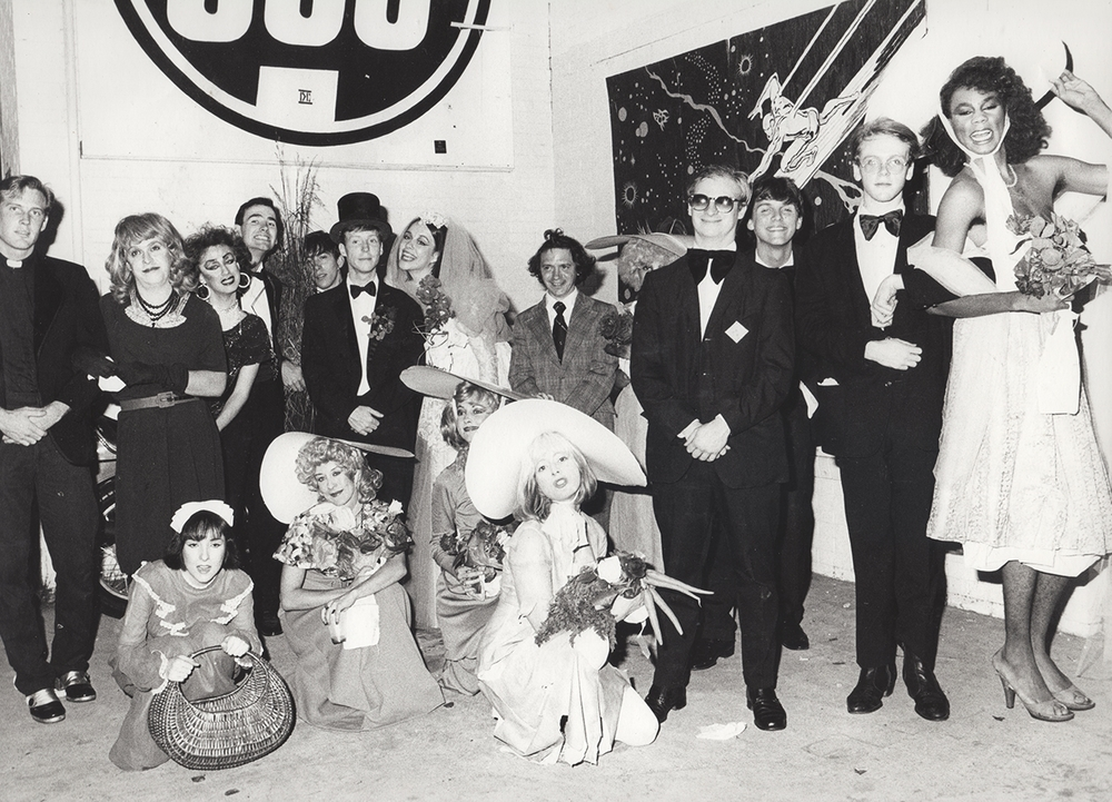 "A group shot from The Now Explosion's 1983 ""Wedding Show"" at 688. The Now Explosion was famous for its themed shows. At this wedding-themed outing, drummer Jon Witherspoon (at center in top hat) and lead singer Lady Clare got ""married."" At right is Wee Wee Pole: David Klimchak, Robert Burke Warren, Todd Butler and RuPaul."