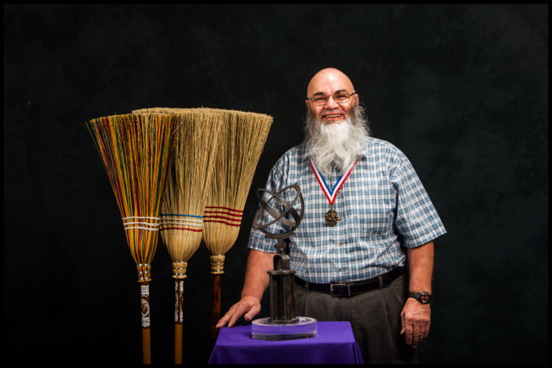 Jack Martin with his brooms and the Tennessee Governor's folklife heritage award they won him.