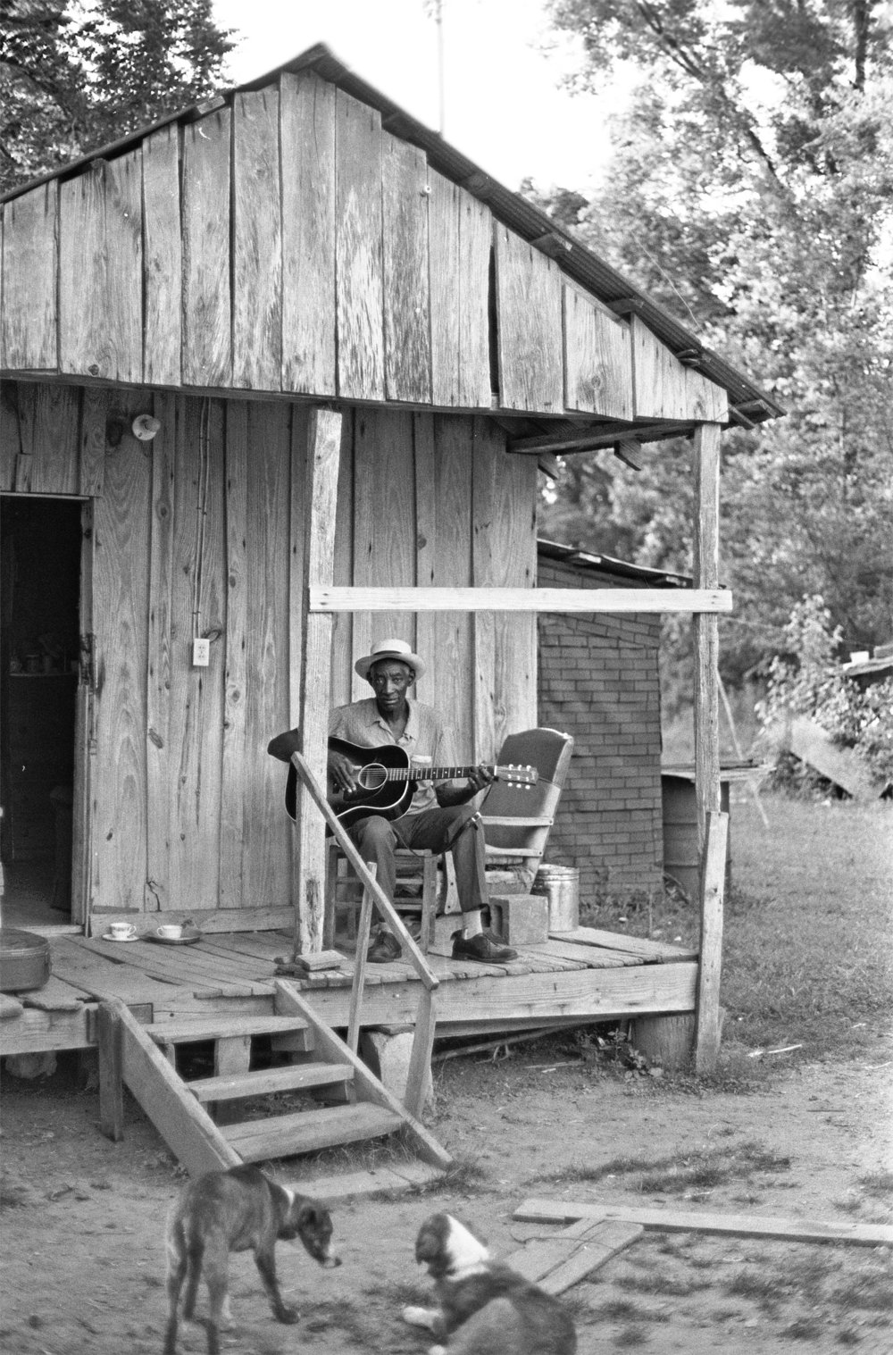 Scott Dunbar plays guitar on his  ont porch.jpg