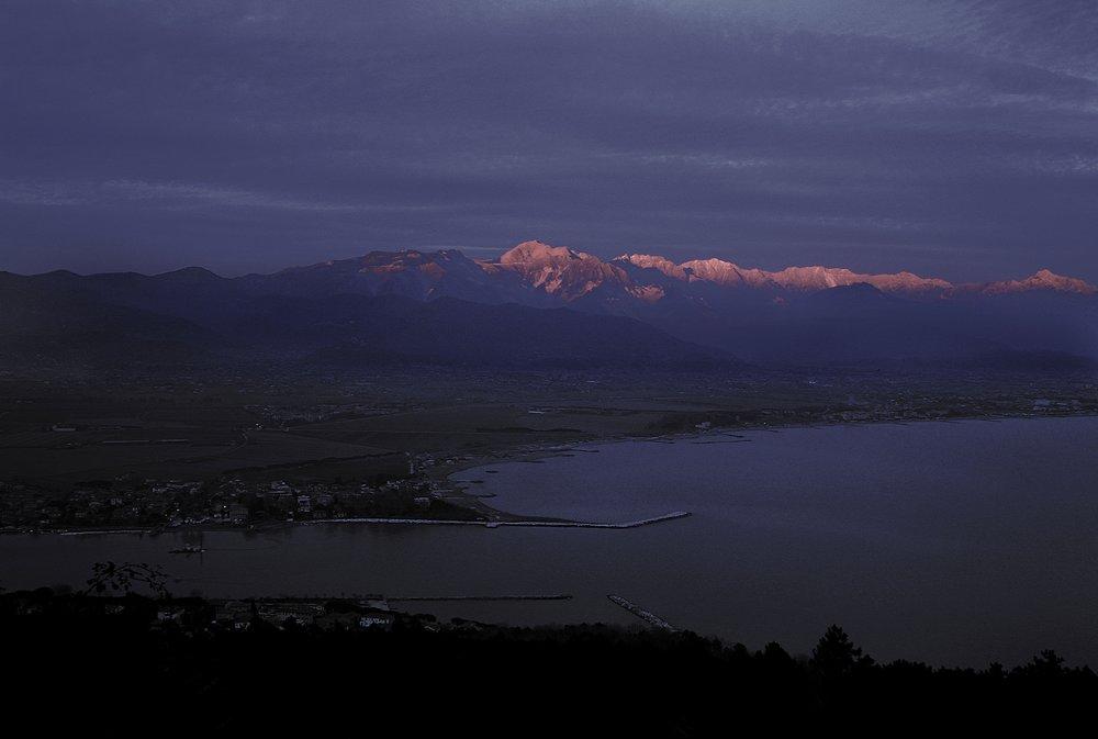 La foce del Magra davanti alle Alpi Apuane, tramonto invernale. Là in mezzo ci sono i resti dell'antica Luni, splendida città romana fiorente fino al II/III secolo d.C.