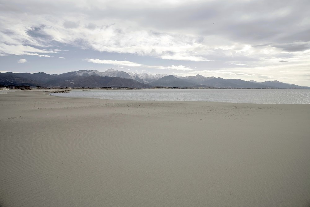 La spiaggia di Fiumaretta stirata dalla tramontana invernale, sullo sfondo il monte Sagro e l'immenso bacino marmifero di Carrara: non tutto il bianco che si vede è neve.