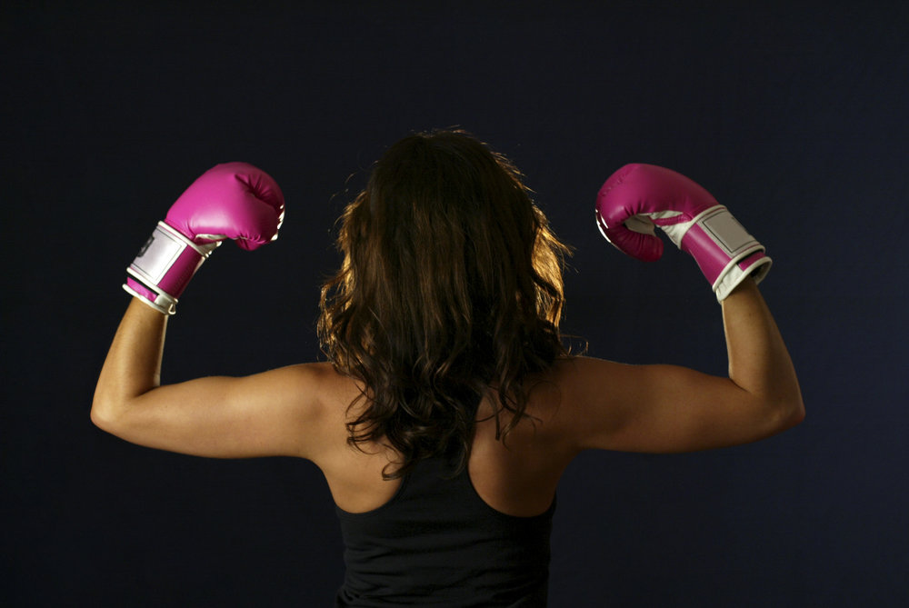 flexing.biceps.pinkboxinggloves.woman.youngadult.exercise.blackbackground.jpg
