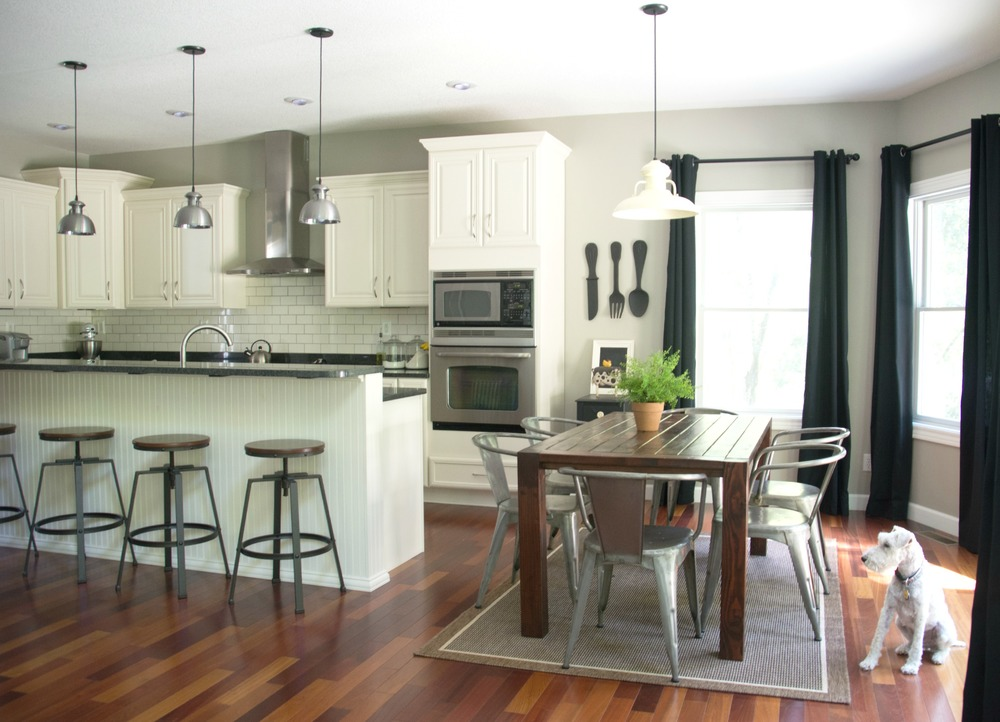 Black curtains.  Black granite. Ivory cabinets. Farmhouse table.  Barnlight lighting.